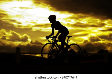 Golden light and sunset Silhouetted female Cyclist  cycling on outdoor track with road bicycle wellness and sport concept