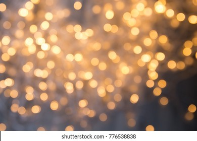A lot of golden lights of a garland, background texture. Blurred bokeh lights in the room. Christmas lights of a garland