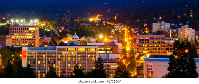 Golden lights illuminate the skyline of a summer evening in Eugene, Oregon as viewed from the top of Skinners Butte.