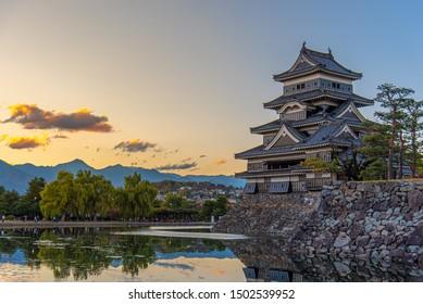 Golden lights sunset reflection scenery at Matsumoto castle in autumn. Landmark in Matsumoto, Nagano,Japan.