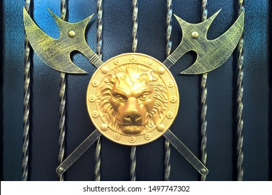 A Golden lion's head on a round shield and two crossed axes. Decoration on the gate of the house. Black background. Horizontal format.