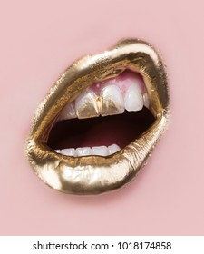 Golden lip make up. Gold paint on lips and teeth. Open mouth and white teeth isolated on pink background. Part of rich face covered in gold. Modern make-up for women. Sensual golden luxury concept