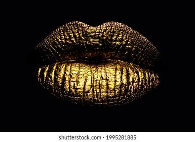 Golden lips closeup. Gold metal art lip. Beautiful makeup. Golden lip gloss on beauty female mouth, closeup. Sensual forms of woman lips.