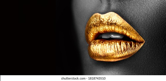 Golden lipstick closeup. Gold metal lips. Beautiful makeup. Sexy lips, bright lip gloss paint on beauty African American model girl's mouth, close-up. Lipstick. Black and white image