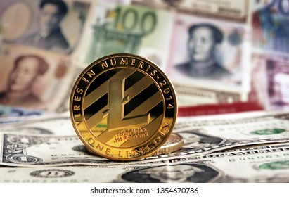 Golden Litecoin agaisnt of different banknotes on background. Cryptocurrency Trading concept