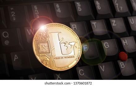 Golden litecoin LTC coin on laptop keyboard