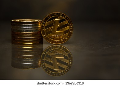 golden Litecoin and pile of coins  on reflective surface