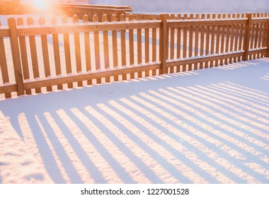 A golden low morning winter sun creating a lens flare and shadows through a new wooden picket fence on a cold day. There is a fresh layer of unspoilt snow on the ground