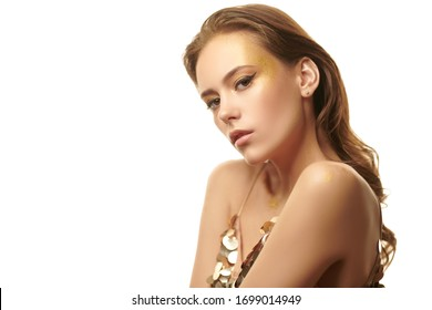 Golden make-up. Gorgeous young woman with golden make-up and in a sparkling gold dress on a background with white light. Party style.