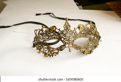 a golden mask with embroidery on a background of white sheets