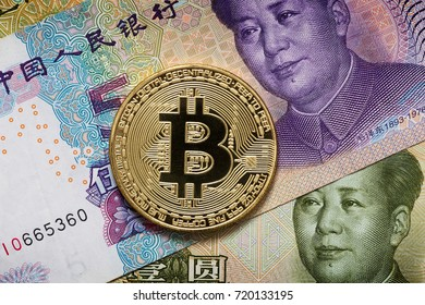 Golden metal bitcoin on a Chineze money. China imposed restrictions on the circulation of bitcoin and other crypto-currencies