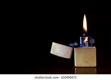 golden metal gasoline lighter on the wooden table, ignited a cigarette lighter, lighter flame on a dark background