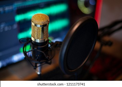 Golden microphone at audio recording, On computer, There is a background audio signal, Close-up.