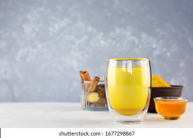 Golden milk and ingredients for its preparation: turmeric, honey, ginger root, cinnamon and badian on a gray background. Masala Haldi Dood. Alternative medicine concept.