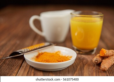 Golden milk turmeric tea with curcuma root and orange powder