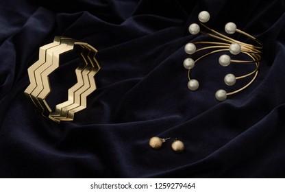 Golden modern Bracelets and pair of earrings on dark blue velvet fabric
