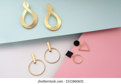 Golden modern stud geometric earrings on colorful background
