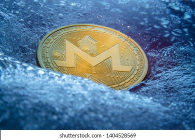 Golden Monero coin, online digital currency frozen in the blue ice. Concept of block chain, crypto market crash. Frozen crypto money, depreciation