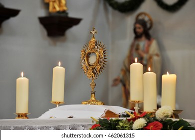Golden monstrance with candles and Jesus' statue in the background.