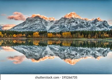Golden mountain peaks and autumn colors reflecting in Wedge Pond in Kananaskis Alberta