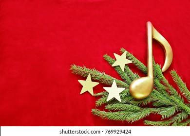 Golden music note on christmas tree  branch with stars on red velvet