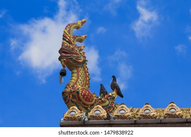 Golden Naga on Art Roof of Buddhist temple with blue sky in Wat Maha Wanaram in Ubon Ratchathani, Thailand, Naga Statue In temple.
