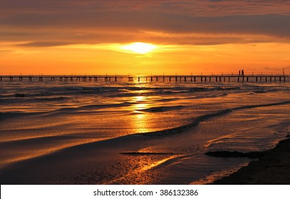 Golden natural sea sunset view of jetty or small bridge at horizon with people  silhouette and orange sky landscape. Sunset or sunrise reflection in nature with sun in clouds above black sea scenery.