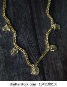 Golden necklace on wooden background. Woman accessoires, fashion concept