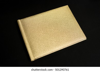 Golden notebook and pen isolated on Black background.