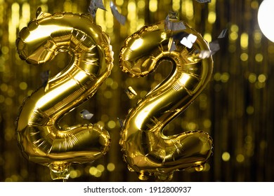 Golden number 22 twenty two made from an inflatable balloon, on a yellow background. One of the complete set of numbers. The concept of birthday, anniversary, date