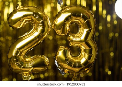 Golden number 23 twenty three made from an inflatable balloon, on a yellow background. One of the complete set of numbers. The concept of birthday, anniversary, date