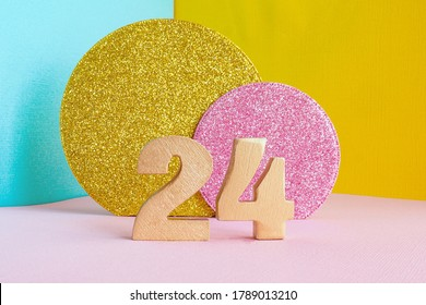 """golden number """"24"""" on a multicolored blue-yellow-pink background and two shiny gold and pink circles. happy birthday greeting card concept."""