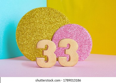 """golden number """"33"""" on a multicolored blue-yellow-pink background and two shiny gold and pink circles. happy birthday greeting card concept."""