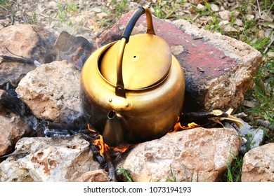 Golden old kettle to boil water on wood fire while camping