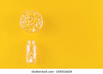 golden omega capsules in a bowl and bottle on yellow background, flat lay