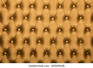 Golden orange capitone textile background, retro Chesterfield style checkered soft tufted fabric furniture diamond pattern decoration with buttons, close up