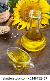 Golden organic oil in a small glass jug, sunflower, sunflower seeds. Agriculture, oil production. Bio and organic concept of the product.