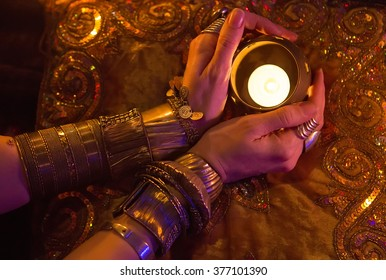 Golden Oriental Jewelry Accessories: Female Hands with beautiful National Indian Jewellery, Eastern Fairy Tale (Harem), Wedding Fashion. Eastern Treasure by Candlelight. Luxury Arabian Interior