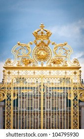 Golden ornate gate of Chateau de Versailles with blue sky and clouds in background. Paris, France, Europe.