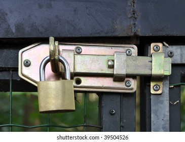 golden padlock on lever, old fence