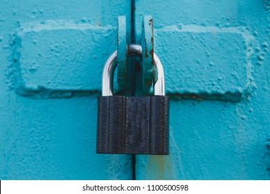 Golden padlock on old blue wooden door