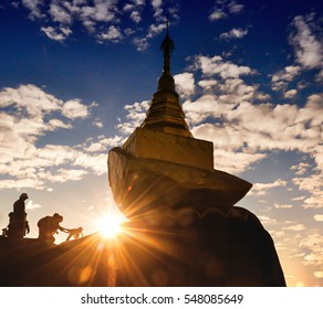 Golden pagoda on rock in golden sunlight shade at dawn or twilight with sky background and silhouette shadow of faithful asian parent on pilgrimage sending their child climbing the cliff to the pagoda