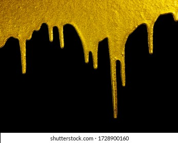 Golden paint dripping liquid paint, isolated on black background. Flowing abstract Gold metallic paint drops close-up. Leaking.gold paint dripping or flowing on black background