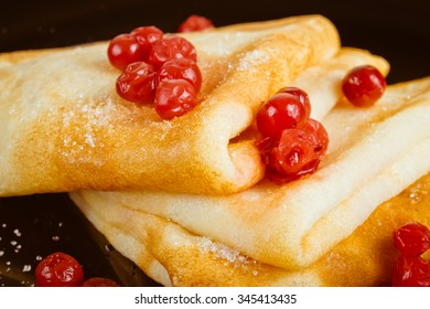 Golden pancakes with lingonberry jam on a dark background