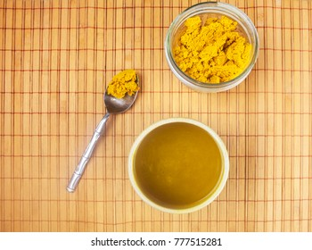 Golden paste in a jar and on a spoon with a cup of turmeric tea shot from above.