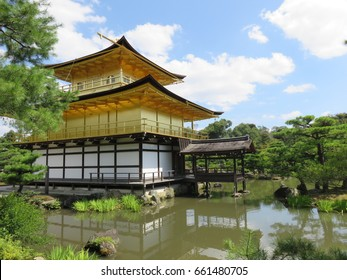 Golden pavilion in a large pond with blue sky at Kinkaku-ji officially named Rokuon-ji (Zen Buddhist temple) in Kyoto, Japan