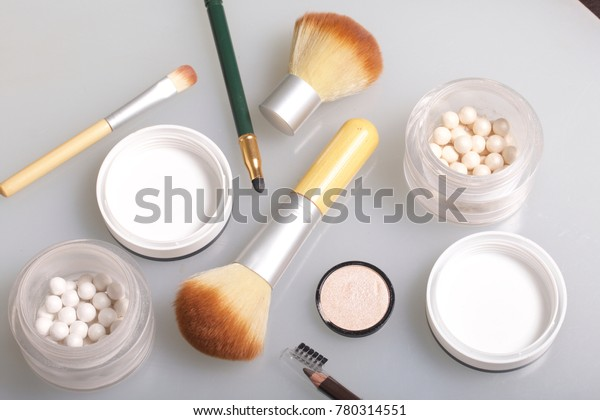 Golden and pearl highlighter in the form of balls in an open jar. Close to the brush for applying cosmetics and cosmetic pencils. On a white background, view from above.