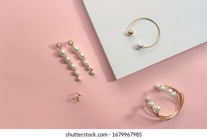 Golden with pearls bracelets and earrings on white and pink background