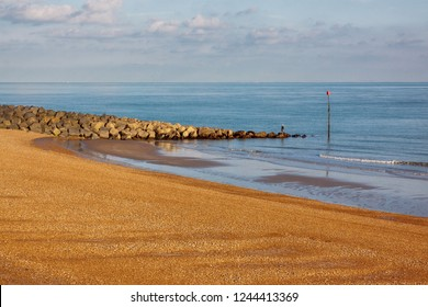 Golden pebble beach and rock groyne blue sea with distant fisherman