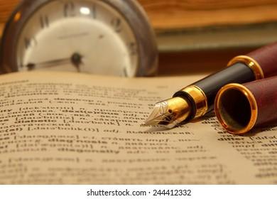 Golden pen on the book